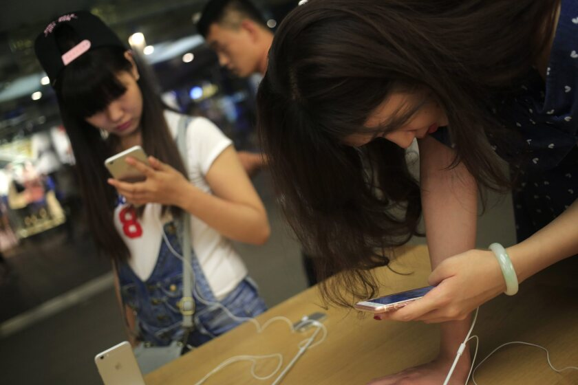 Customers look at mobile phones in an Apple Store in Beijing. Apple Inc. has been ordered by Beijing's intellectual property regulator to stop sales of the iPhone 6 and iPhone 6 Plus models in the city.