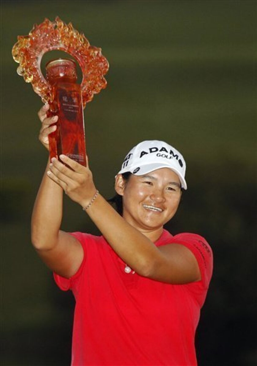 FILE - In this Oct. 23, 2011, file photo, Yani Tseng, of Taiwan, holds up her championship trophy on the 18th hole after the final round of the LPGA Taiwan Championship at the Sunrise Golf and Country Club in Taoyuan, Taiwan. Tseng has a tradition on Chinese New Year to give her house a thorough cleaning, and decided to start with the trophy cabinet_she is coming off a blockbuster season in which she won 12 times around the world, including the first four tournaments she played. (AP Photo/Wally Santana, File)