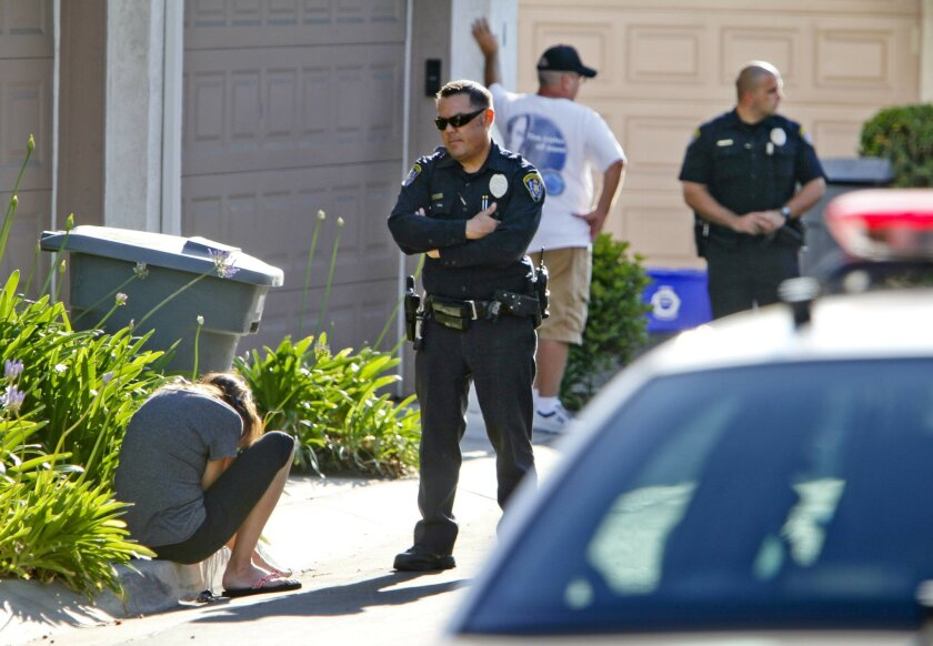 A woman sits on the curb as police talk to her while they investigate the scene of an accidental shooting of a young boy near Scripps Poway Parkway in San Diego on Tuesday. Police did not handcuff, but took away the man standing in the background.