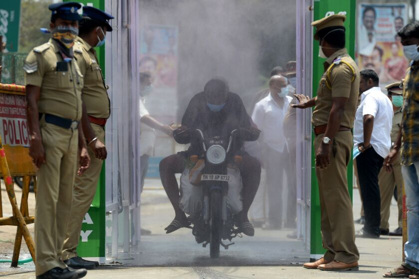 A motorist rides through a spray of disinfectant to protect against the coronavirus in Chennai, India, on Sunday.