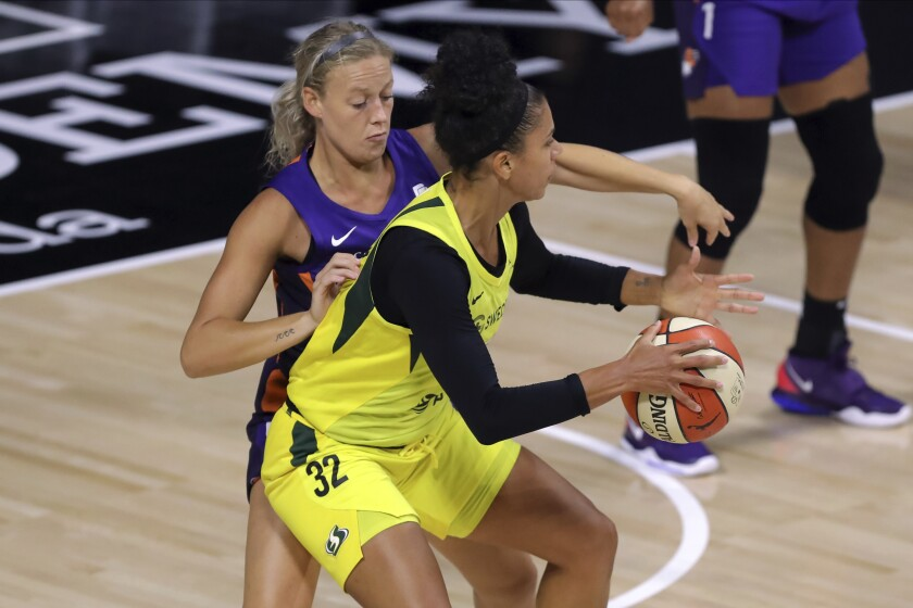 Seattle Storm's Alysha Clark (32) backs into the defense of Phoenix Mercury's Sophie Cunningham during the first half of a WNBA basketball game Saturday, Aug. 8, 2020, in Bradenton, Fla. (AP Photo/Mike Carlson)