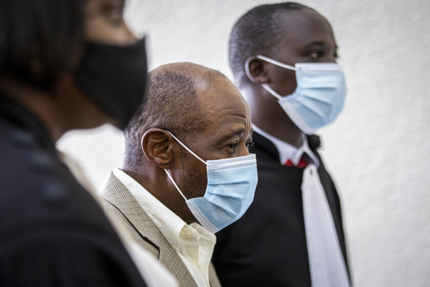 """FILE - In this Monday, Sept. 14, 2020 file photo, Paul Rusesabagina, center, whose story inspired the film """"Hotel Rwanda"""" for saving people from genocide, appears at the Kicukiro Primary Court in the capital Kigali, Rwanda. Rwandan prosecutors on Thursday June 17, 2021, requested a life sentence for the man who inspired the film """"Hotel Rwanda"""" as he faces terrorism charges, while his family asserts that he faces mistreatment and an unfair trial. (AP Photo/File)"""