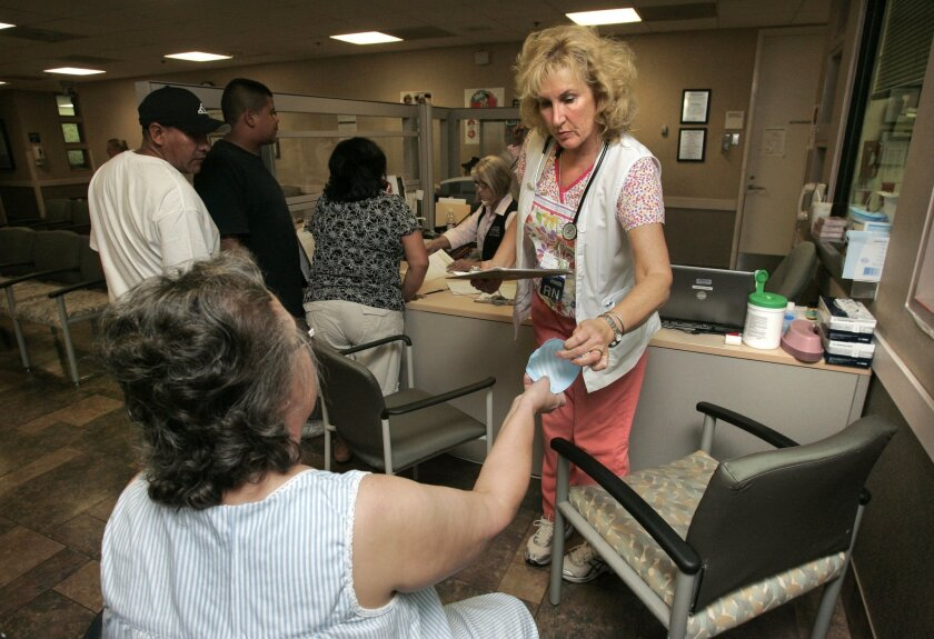 Nurse Margaret Thomas handed out a mask yesterday at Palomar Medical Center's Quick View station. The station is used to quickly assess the condition of patients. (Charlie Neuman / Union-Tribune)