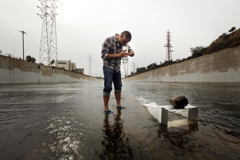 Environmental activist and scientist Marcus Eriksen collects a sample in 2014 of plastic particles making their way via the Los Angeles River to the ocean, where some will join the sediment. Some scientists say plastic deposits and other detritus of human development mark the beginning of a new geologic era.