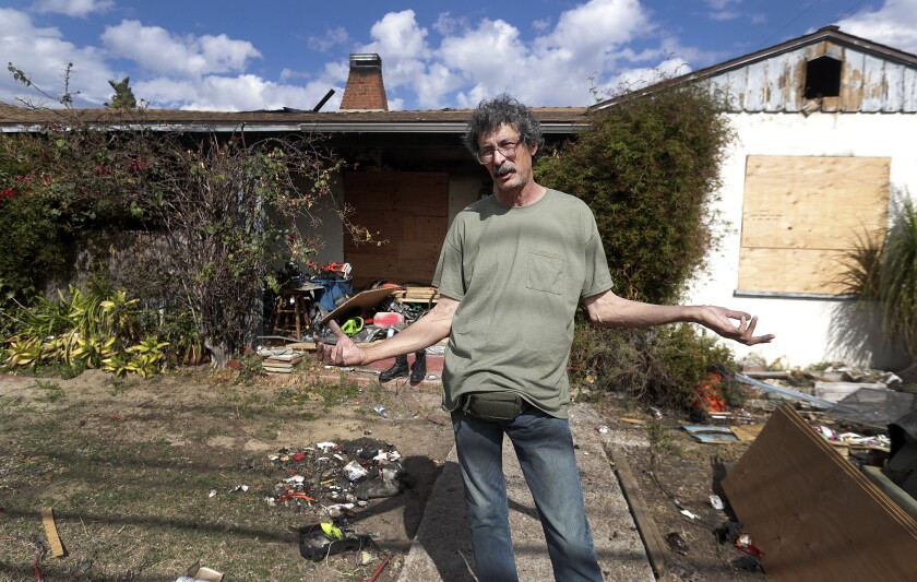 """George Contreras stands in front of his burnt-out house on Lake Street in Burbank. He said he finds himself wondering, """"What else am I supposed to do?"""" The 60-year-old lost an 8-year-old dog named Blackie in a fire on Feb. 13 as well the mementos of family members who have passed away."""
