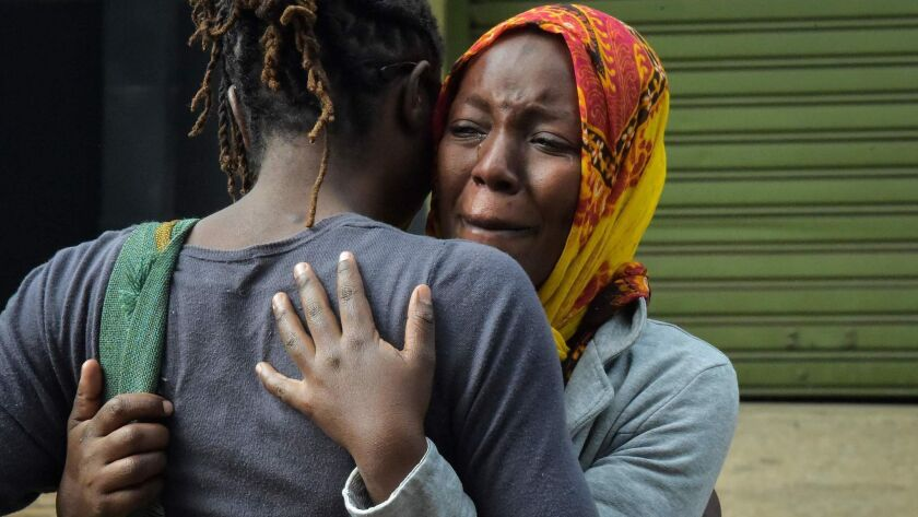 A woman cries in the arms of a relative in Nairobi on Jan. 16 while identifying the bodies of the victims after an attack on a hotel complex.