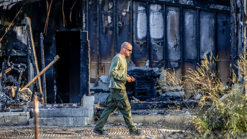 Riverside Sheriff investigator in front of the charred remains of board-and-care facility in Temecula, where firefighters found the remains of five people inside in late August.