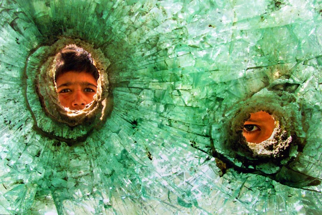 چهره دو پسر از سوراخ گلوله در شیشه شکسته دیده می شود