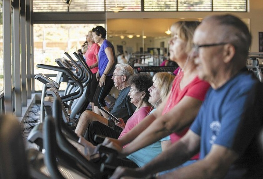 People use the machines inside the fitness center at the OASIS Senior Center in Newport Beach in 2014.