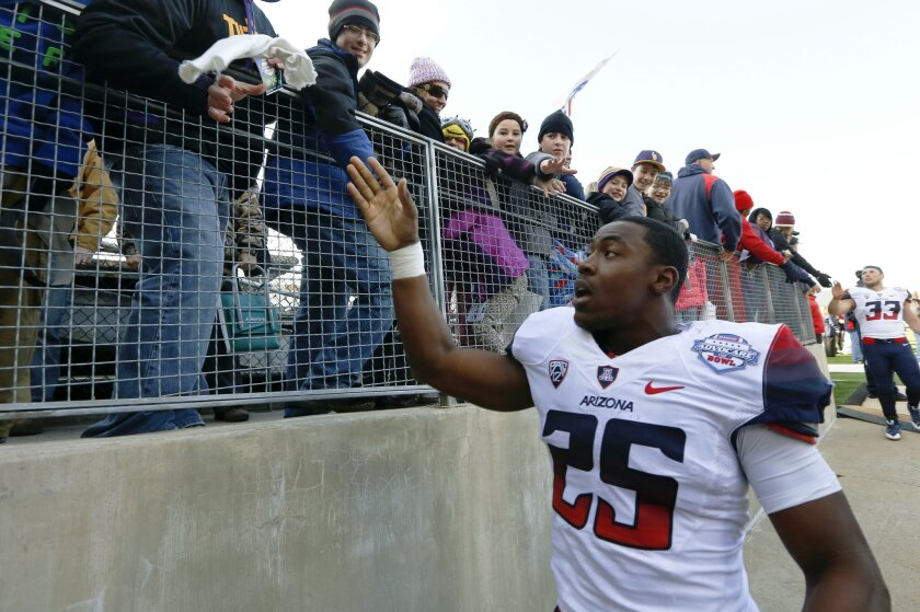 Arizona running back Ka'Deem Carey (25)celebrates with fans after beating Boston College, 42-19, in the AdvoCare V100 Bowl NCAA college football game, Tuesday, Dec. 31, 2013, at Independence Stadium in Shreveport, La.  (AP Photo/Rogelio V. Solis)