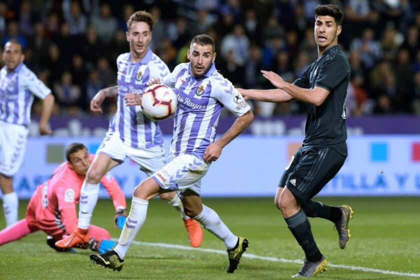 El delantero del Real Madrid Marco Asensio (d) persigue un balón ante varios defensores del Real Valladolid, durante el partido de Liga en Primera División disputado en el estadio José Zorrilla. EFE