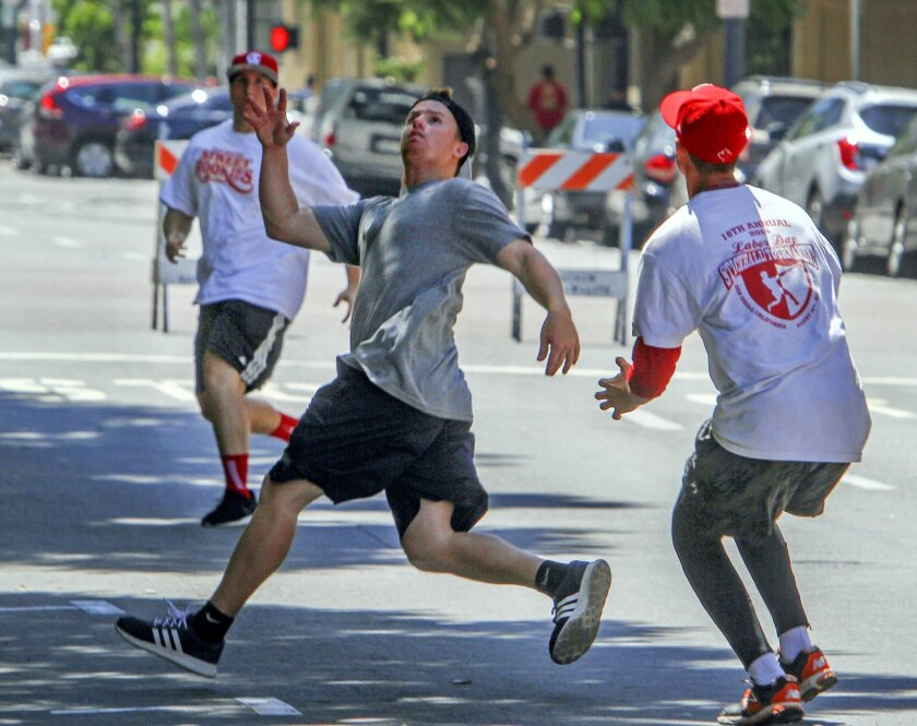 Bare-handed outfielders from the San Diego Street Rookiezs try to make a play Sunday during the Labor Day stickball tournament in Little Italy.