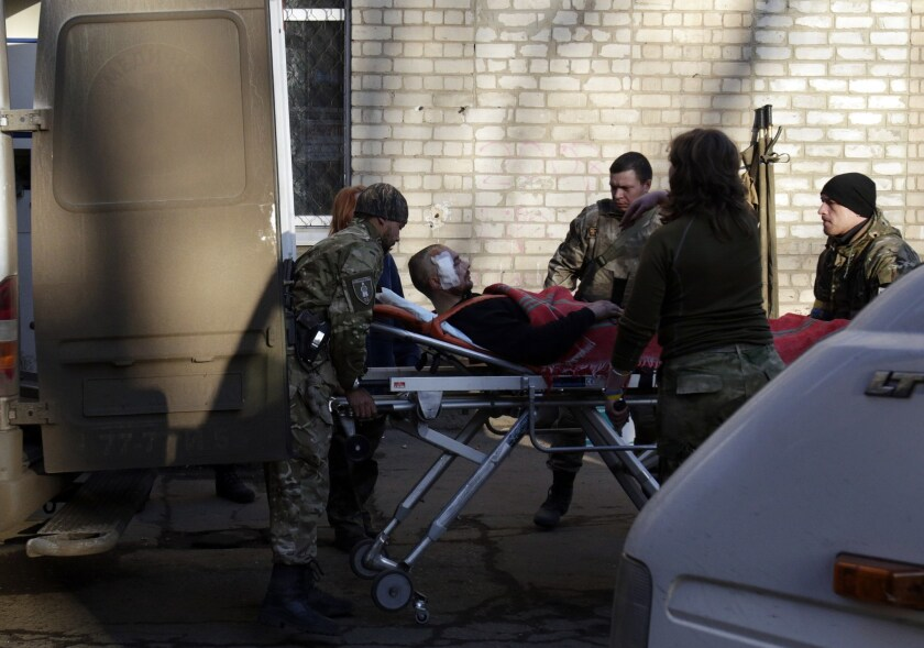 Ukrainian troops load an injured man into an ambulance in the eastern Ukrainian city of Artemivsk on Friday. At least 25 people died and dozens were injured in intensified fighting a day after a new cease-fire was signed.