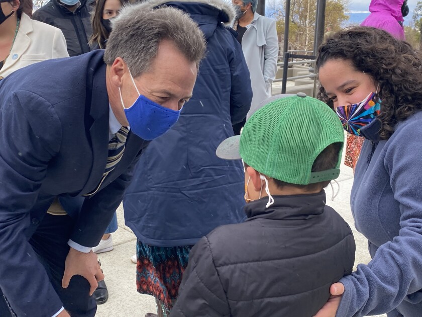 Montana Gov. Steve Bullock, a Democrat running for U.S. Senate, meets Archer James, 6, as his mother, Lisa, looks on.