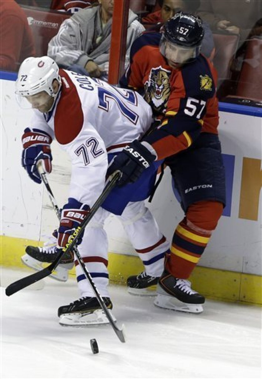 Montreal Canadiens right wing Erik Cole (72) vies for the puck with Florida Panthers center Marcel Goc (57), of Germany, during the second period of an NHL hockey game Thursday, Feb. 14, 2013, in Sunrise, Fla. (AP Photo/Wilfredo Lee)