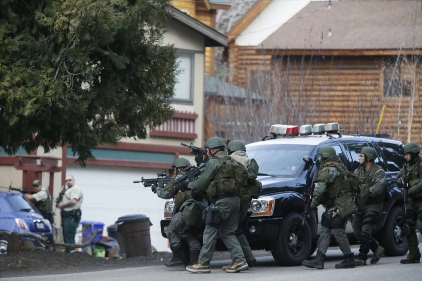 A SWAT team enters a home in Big Bear during the search for Christopher Dorner. Law enforcement agencies swarmed the mountain community after the suspect's burned truck was found on a remote road.
