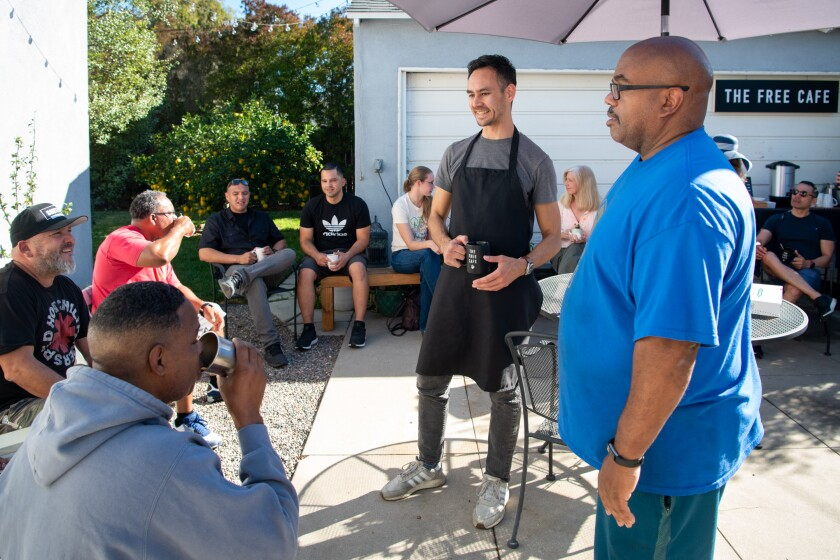 Michael Rippens, left, talks to neighbors at the Free Cafe, a monthly gathering held in his Leimert Park backyard.