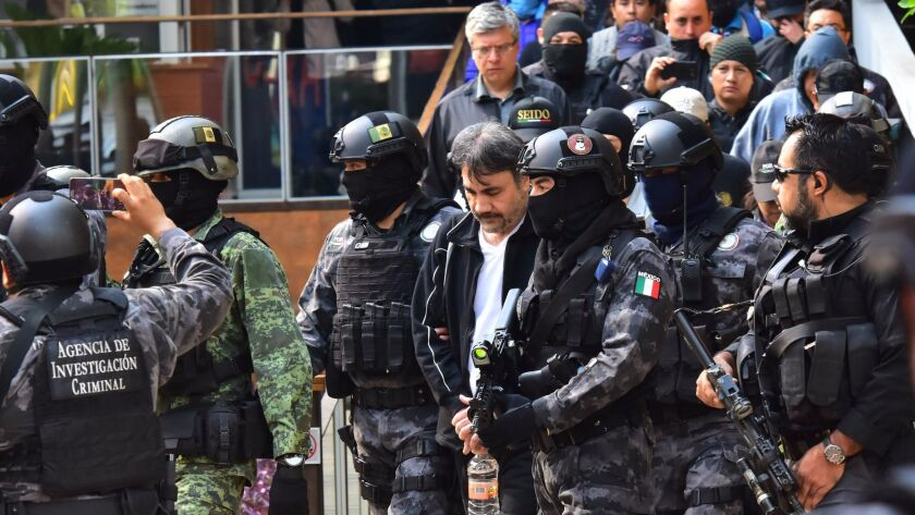 """Agents of the Criminal Investigation Agency and Mexican soldiers escort Damaso Lopez, senior lieutenant of jailed drug lord Joaquin """"El Chapo"""" Guzman, after arresting him May 2, 2017, in Mexico City."""
