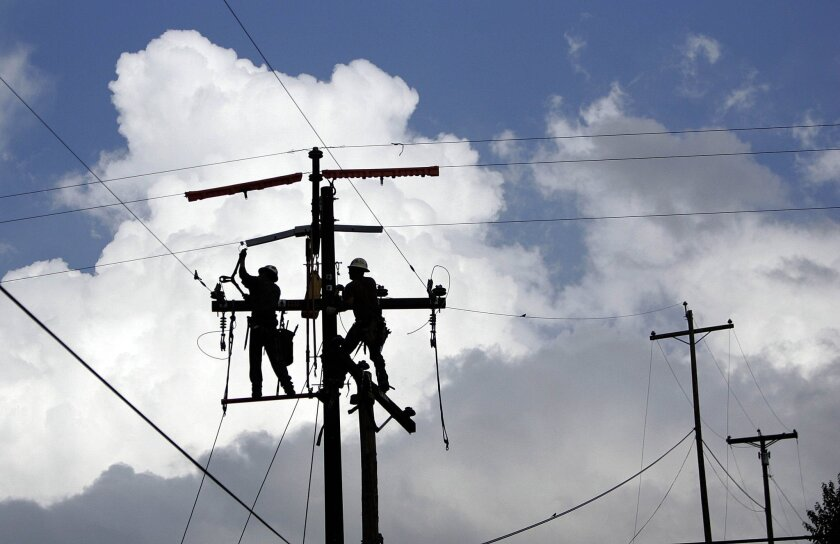 Crews replace wood power poles with fire-resistant steel ones in 2011.