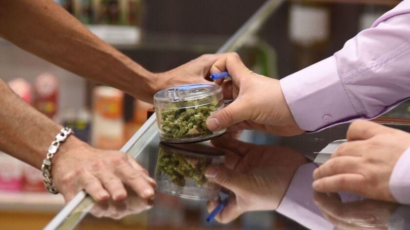 A customer peruses marijuana buds at the Green Pearl Organics dispensary in Desert Hot Springs, Calif., on Jan. 1.