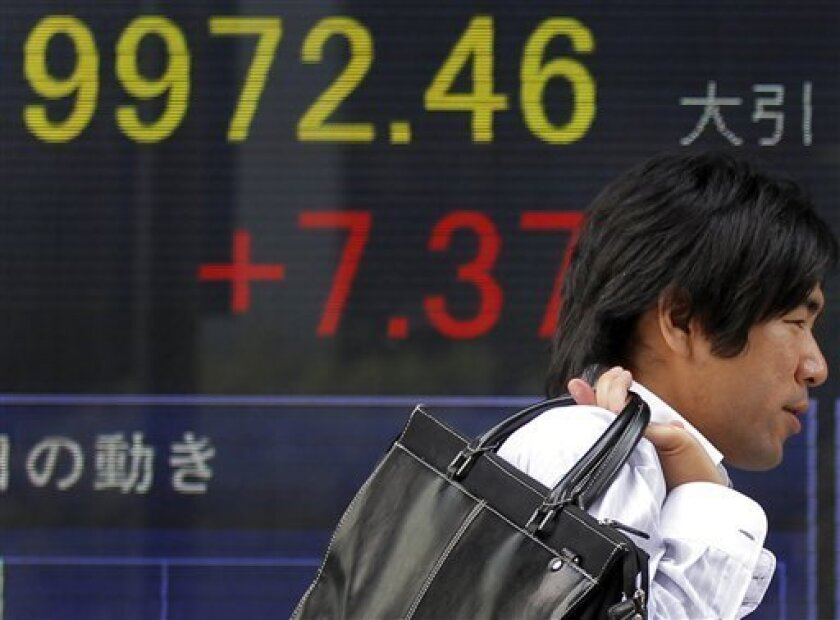 A man walks outsdie a securities firm in Tokyo, Japan, Tuesday, July 5, 2011. Japan's Nikkei 225 dropped narrowly to 9,962.02, a small retreat from Monday's two-month high as investors sought to cash in profits a day after the index briefly rose above the 10,000 mark for the first time since May 5. (AP Photo/Itsuo Inouye)