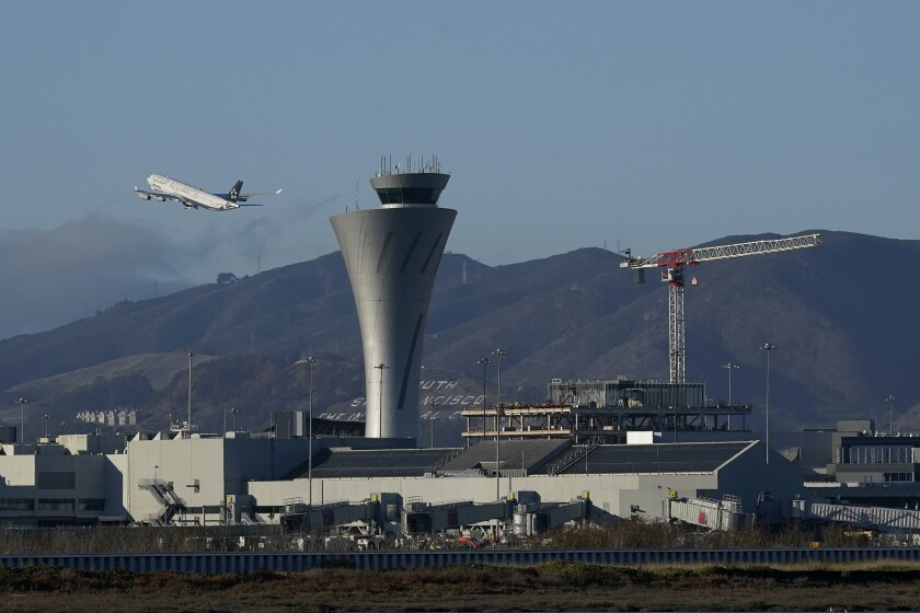 FILE - In this Nov. 24, 2020, file photo, a plane takes off behind the air traffic control tower at San Francisco International Airport in San Francisco. San Francisco is requiring all workers at San Francisco International Airport to get vaccinated against COVID-19. Employees who are exempt must undergo weekly testing. The mandate announced Tuesday, Sept. 21, 2021, applies to roughly 46,000 on-site personnel, including employees of contractors and retail tenants. (AP Photo/Jeff Chiu,File)