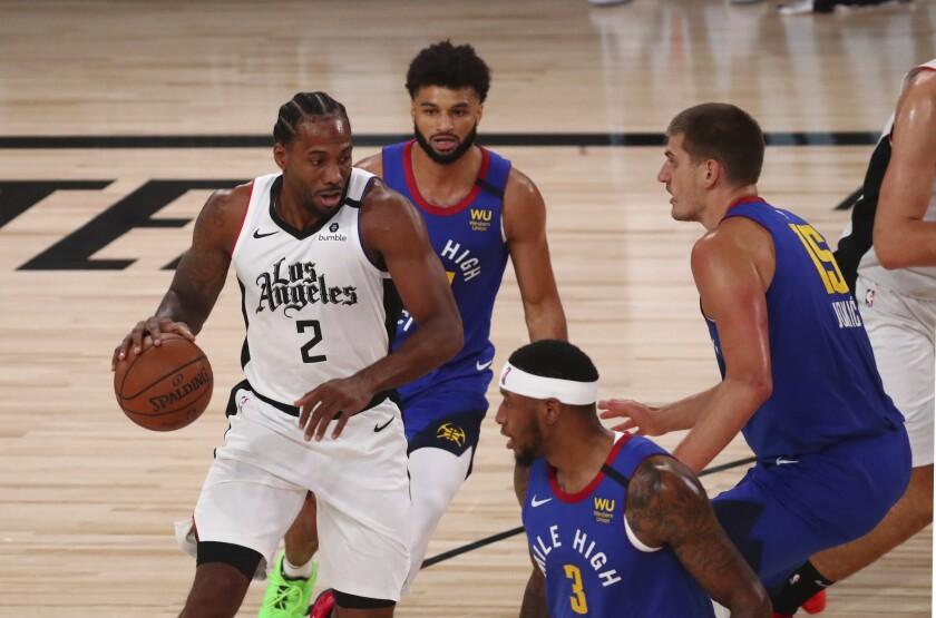 Clippers star Kawhi Leonard faces the double-team defense of Nuggets center Nikola Jokic and guard Jamal Murray on Aug. 12.
