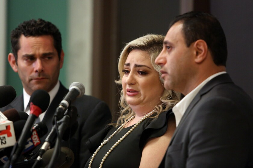 Anni Manukyan, center, speaks with her husband, Ashot Manukyan, right, during a news conference in Los Angeles about the alleged mix-up over a mishandled IVF treatment.