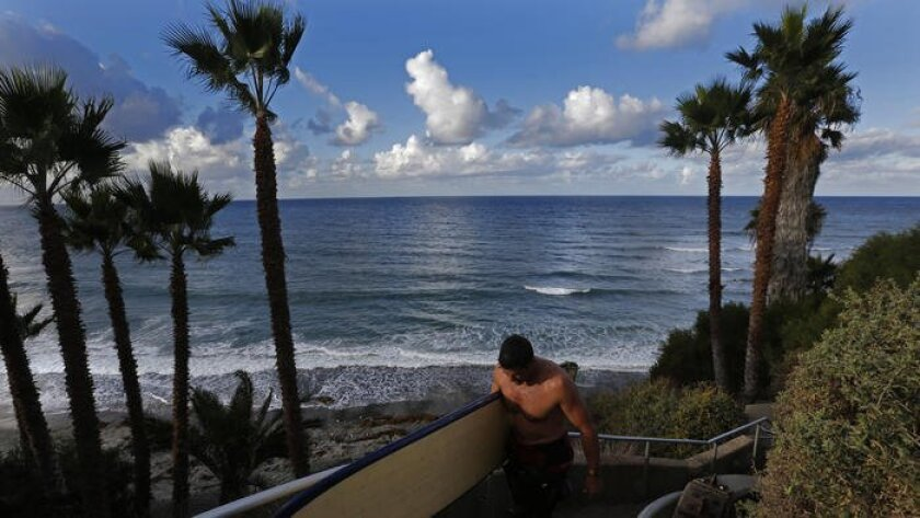 Dr. Johnny Greenfield carries his surfboard up from Swami's beach in Encinitas, where two surfers died recently at the well-known north San Diego County spot.