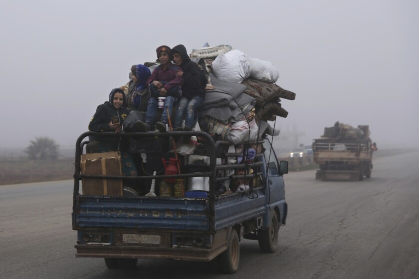 Civilians ride in a truck on Monday as they flee Maaret al-Numan, Syria, ahead of a government offensive.