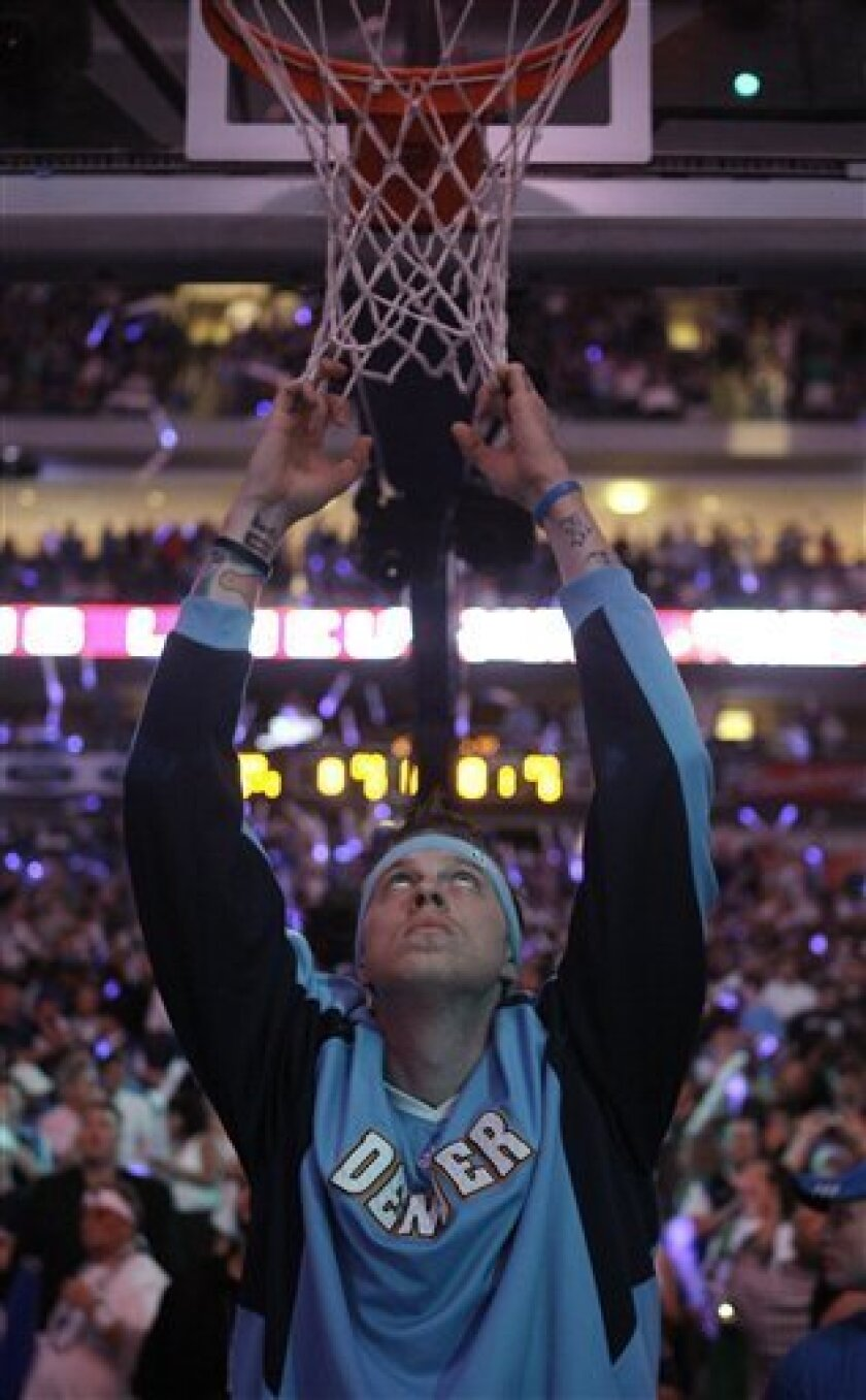 Denver Nuggets center Chris Andersen hangs from the net before Game 3 of the NBA basketball Western Conference semifinals against the Dallas Mavericks, Saturday, May 9, 2009, in Dallas. (AP Photo/Matt Slocum)