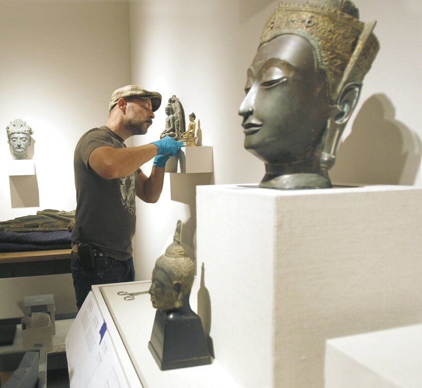 The San Diego Museum of Art's head preparator and assistant registrar James Gielow installs works in the first of three galleries that have been reworked.