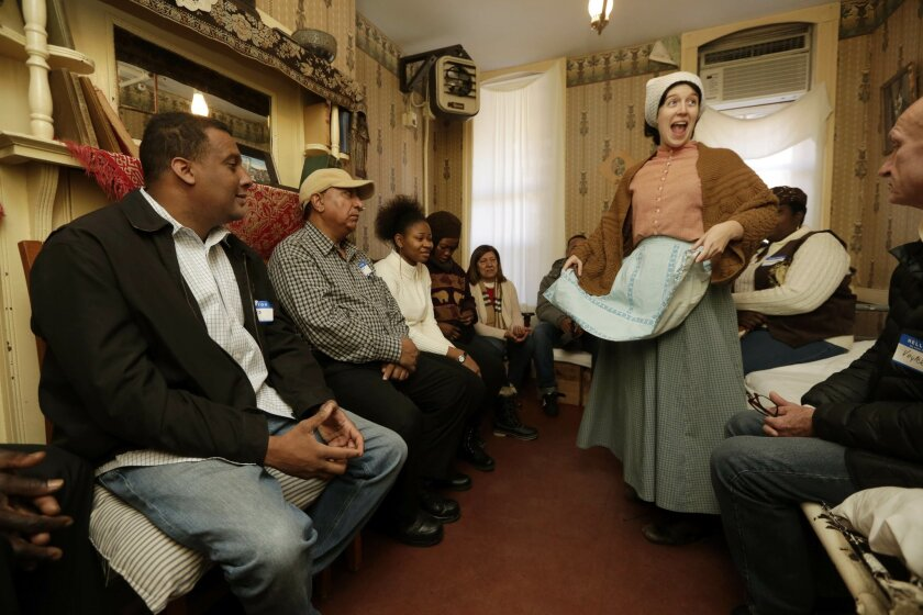 Kathleen Fletcher, portraying 14-year-old tenement resident Victoria Confino, talks with immigrants during Shared Journeys, a workshop in English for Speakers of Other Languages, or ESOL, run by the Tenement Museum, on New York's Lower East Side, Friday, Nov. 21, 2014. Held in a restored 4-story tenement building that housed 7,000 working class immigrants between 1863 and 1935, the program invites them to learn about immigrants of the past by visiting the restored tenement apartments and then sharing and talking about their own experiences. (AP Photo/Richard Drew)