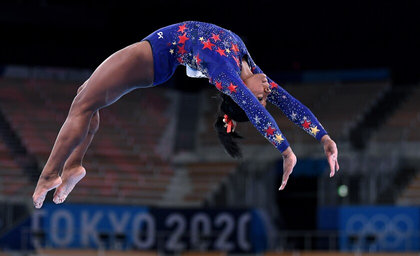 U.S. gymnast Simone Biles arches in mid-air at the Tokyo Olympics.