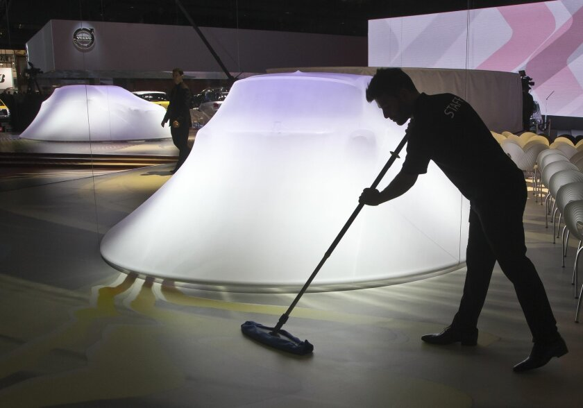 Worker cleans the floor next to a Fiat 500 X, in preparation for the press conference during the press day at the Motor Show in Paris, France, Thursday, Oct. 2, 2014. European carmakers are hoping to impress with new models at this week's Paris Motor Show and prove they have come out stronger from years of economic trouble and cost-cutting. (AP Photo/Michel Euler)