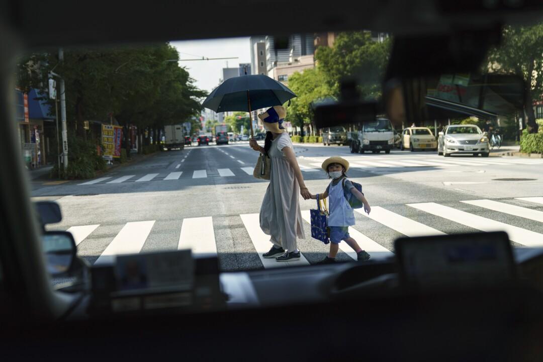 زنی با چتر دست کودک را در یک خیابان آفتابی گرفته است.