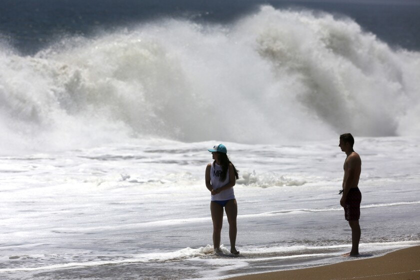 People watch the waves at the Wedge in Newport Beach.