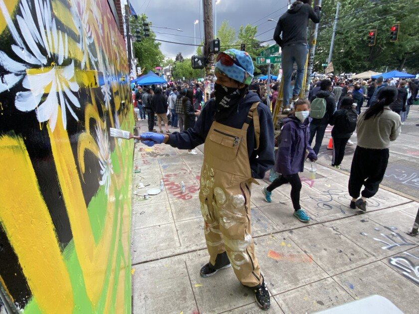 """Procter adds a flower to his mural in the area initially dubbed the """"Capitol Hill Autonomous Zone."""""""