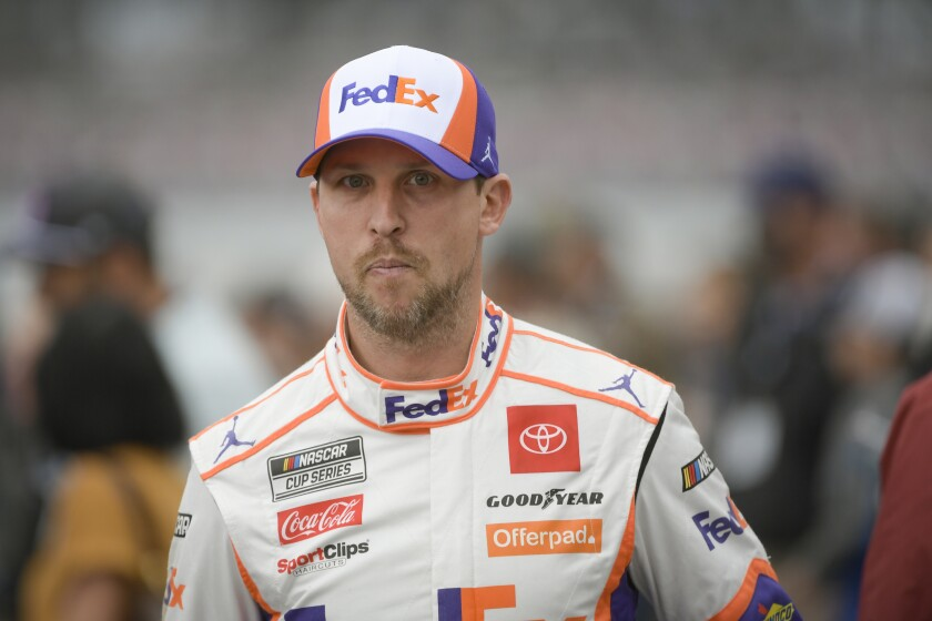 Denny Hamlin makes his way to his car for a NASCAR Cup series auto race Sunday, Oct. 3, 2021, in Talladega, Ala. The race was postponed until Monday due to wet weather. (AP Photo/John Amis)