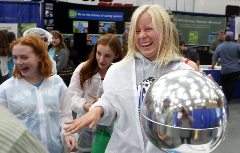 Susanne Taavitsainen , 14, of Escondido laughs along with fellow students as she gets a shock while learning about static electricity at the 2012 High Tech Fair Wednesday at the Del Mar fairgrounds.