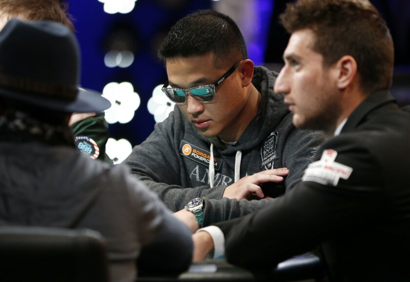 Patrick Chan, center, looks at his chips at the World Series of Poker Sunday, Nov. 8, 2015, in Las Vegas. Sunday night was the first of three days of poker-playing before crowning a new champion and awarding more than $7 million to the winner. (AP Photo/John Locher)