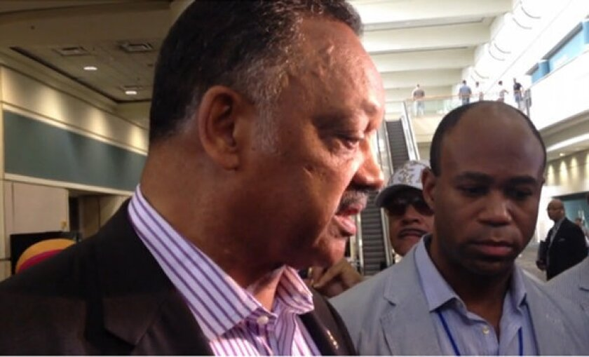 Civil rights leader the Rev. Jesse Jackson holds an impromptu news conference outside the NAACP convention in Orlando.