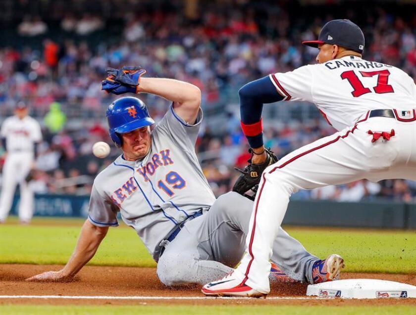 El jardinero derecho de los Mets de Nueva York Jay Bruce (i) toca tercera base antes de que Johan Camargo (d) de los Bravos de Atlanta lograra lanzar, durante un partido. EFE/Archivo