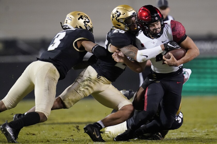 San Diego State quarterback Jordon Brookshire is dragged down after a short gain against Colorado.
