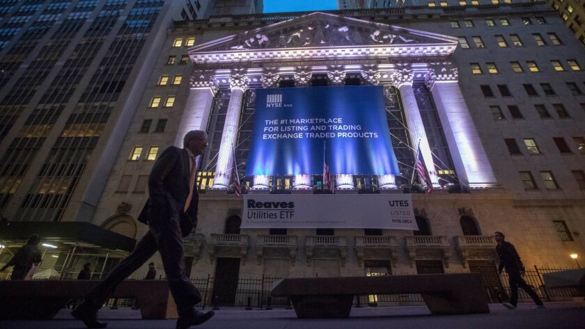 A pedestrian passes the New York Stock Exchange in lower Manhattan, where stocks have risen to record levels since the election.