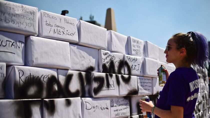 """An activist writes the word """"racism"""" on a mock border wall during an anti-Trump march in Mexico City on Feb. 12."""