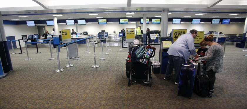 A family completes their self check-in while nearly all other lines are empty at the Hollywood Burbank Airport on Tuesday, March 17. The number of passengers at the airport were diminished by 50% or more due to the coronavirus outbreak.