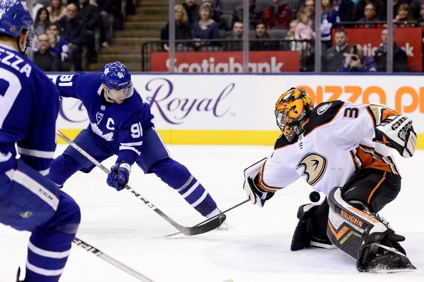 Toronto Maple Leafs center John Tavares (91) knocks the puck past Anaheim Ducks goaltender John Gibson (36) to score in overtime during an NHL hockey game Friday, Feb. 7, 2020, in Toronto. (Frank Gunn/The Canadian Press via AP)