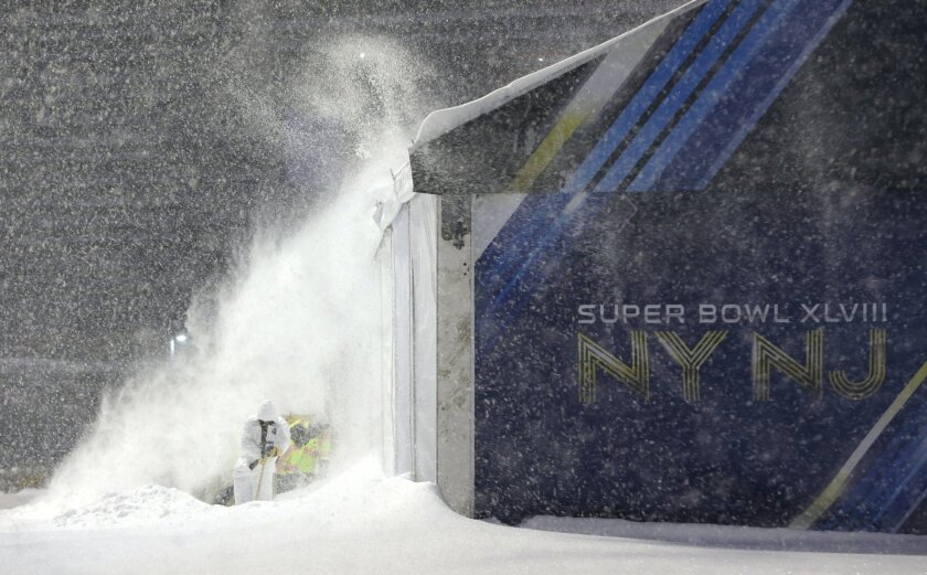 Workers shovel snow near a tent which will be used as an access point into Super Bowl XLVIII as crews prepare MetLife Stadium during a snow storm, Tuesday, Jan. 21, 2014, in East Rutherford, N.J. The NFL football title game, held Feb. 2, will be the first Super Bowl held outdoors in a city where it