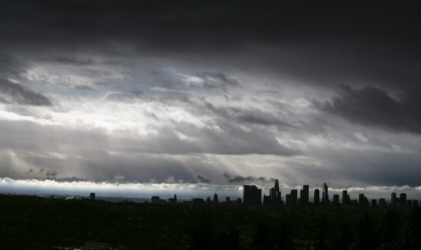 A bank of gray clouds hangs over a darkened Los Angeles skyline.
